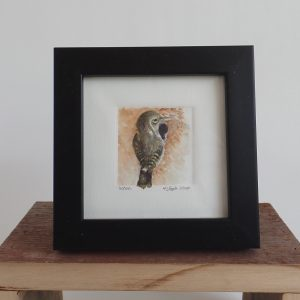 An original tiny watercolor painting of a wren sitting at the opening of a gourd wren house.