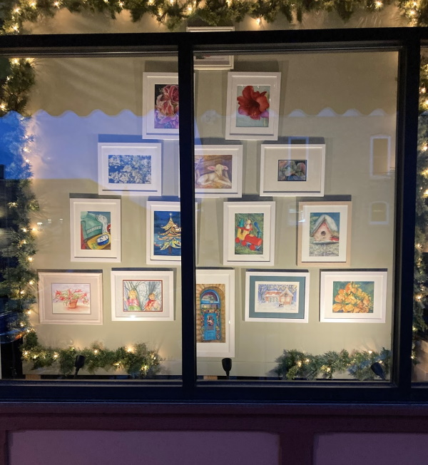 Holiday paintings displayed in a lighted window