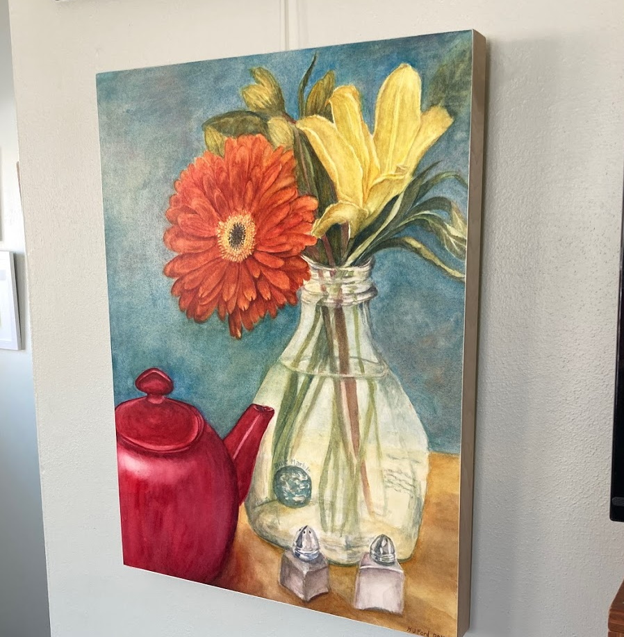 An original watercolor painting of a gerbera daisy and red teapot mounted on cradled board and sealed with wax