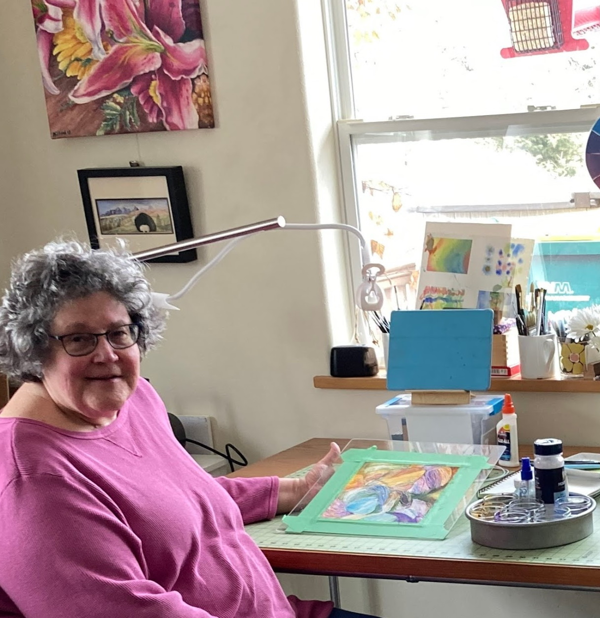 Katherine Ford in her studio with a watercolor painting of yarn skeins