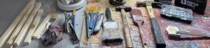 Workbench with hammer, paintbrush and wood.
